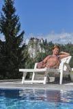 Weiß gebräunte ein Sonnenbad nehmende Frau Ausgeblutetes Schloss im Hintergrund Stockfoto