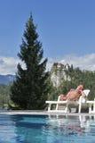 Weiß gebräunte ein Sonnenbad nehmende Frau Ausgeblutetes Schloss im Hintergrund Stockfotografie