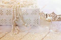 Weiß perlt Halskette, Diamanttiara und Parfümflasche Stockfotografie