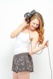 Weiblich, den Spaß habend, der auf Kopfhörer hört Stockfotos