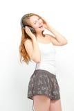 Weiblich, den Spaß habend, der auf Kopfhörer hört Stockfotografie