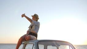 Weiblich an der alten Maschine fotografierte am Telefon auf Hintergrund des Himmels, selfphoto der jungen Frau zum Retro- Auto stock footage