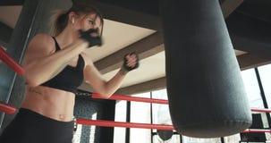 Weiblich, eine boxende Tasche mit Boxhandschuhen an der Turnhalle lochend stock footage