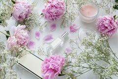 Weiblich, flache Lage Schönheit Blogger - Parfümflasche, Pfingstrosen, Gypsophilablumen auf Marmorhintergrund stockfotografie