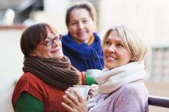 Weiblich, Tee auf Terrasse trinkend Stockbild