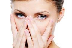 Weibliche Abdeckung der Schönheit durch Hände ihr sauberes Gesicht Lizenzfreies Stockbild