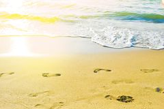 Weibliche Abdrücke auf dem Strand gegen zu Meer lizenzfreie stockfotos