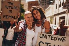 Weibliche Aktivisten mit Plakaten und Friedenszeichen lizenzfreie stockfotos