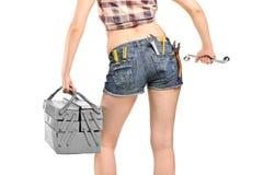 Weibliche Arbeitskraft, die einen Schlüssel und einen Werkzeugkasten anhält Lizenzfreie Stockbilder