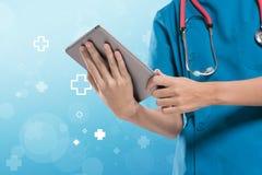 Weibliche Arztkrankenschwester, die Tablette auf blauem Hintergrundabsolventen verwendet Lizenzfreies Stockfoto