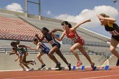 Weibliche Athleten, die von den Startblöcken sich entfernen Lizenzfreie Stockfotografie