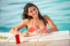 Weibliche Aufstellung des verlockenden Brunette im Swimmingpool mit Stück von Lizenzfreie Stockbilder