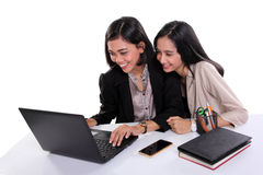 Weibliche Büroangestellte, die zusammen Laptop verwenden lizenzfreie stockbilder