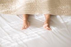 Weibliche barf??ig oder F??e auf Schlafzimmer unter Decke morgens, Draufsicht, kopieren Raum f?r Text lizenzfreies stockfoto