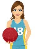 Weibliche Basketball-Spielerholdingkugel Lizenzfreie Stockfotos
