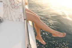 Weibliche Beine außerhalb der Yacht unter warmem Sonnenuntergangaufflackern Stockbild