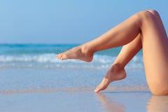 Weibliche Beine auf Seehintergrund Lizenzfreie Stockbilder