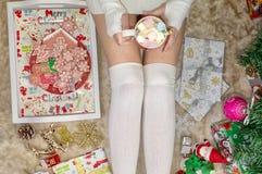 Weibliche Beine, das Mädchen hält einen Becher Eibische Nahaufnahme lizenzfreie stockfotos