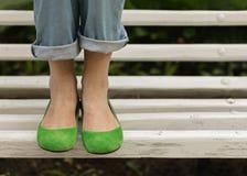 Weibliche Beine in den Blue Jeans und in den grünen Schuhen auf einer weißen Bank Lizenzfreie Stockfotografie