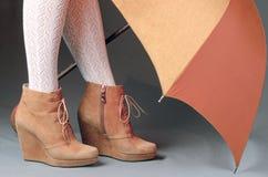 Weibliche Beine in den braunen Velourslederstiefeln unter einem Regenschirm auf einem grauen BAC Stockbilder