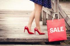Weibliche Beine in den eleganten roten Schuhen mit Fersen auf einer Holzbrücke a Stockbild