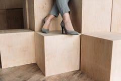 Weibliche Beine in den grauen Fersen auf hölzernen Würfeln Stockbild