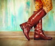 Weibliche Beine in den hohen braunen Lederstiefeln Stockfotos