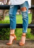 Weibliche Beine in den Jeans und in den Schuhen mit Fersen Stockfotos