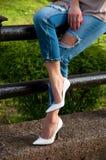 Weibliche Beine in den Jeans und in den weißen Schuhen mit Fersen Stockfoto
