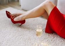 Weibliche Beine in den roten Schuhen und ein rotes Kleid und ein Glas Champagner neues Jahr, Geburtstag, Feiertagskonzept lizenzfreies stockbild