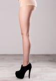 weibliche Beine in den schwarzen Fersen Stockfotos