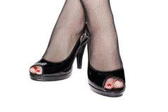 Weibliche Beine in den schwarzen Schuhen lokalisiert Stockfotos
