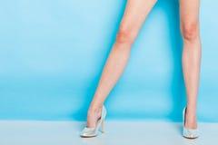 Weibliche Beine in den silbernen Schuhen der hohen Absätze Lizenzfreies Stockfoto
