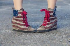 Weibliche Beine in den Turnschuhen mit dem Design der amerikanischen Flagge an Lizenzfreies Stockbild