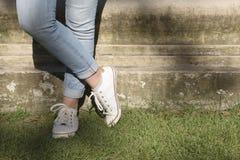 Weibliche Beine, die auf einem Flecken des Grases stehen Lizenzfreie Stockbilder