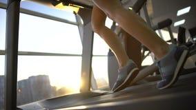 Weibliche Beine, die auf Turnhallentretmühle, Sportfrau aufwärmt vor Training laufen stock footage