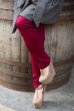 Weibliche Beine, die beige Schuhe auf Plattform- und marsalahosen tragen Lizenzfreies Stockbild