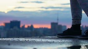 Weibliche Beine, die Dachspitzengebäude, Jugendlichen genießt hohe Ansicht des Stadtsonnenuntergangs gehen stock video