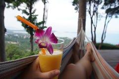 Weibliche Beine, die in der Hängematte mit Mango-Cocktail POV schwingen lizenzfreie stockfotografie