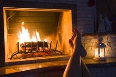 Weibliche Beine, die sich zu Hause Kamin aalen Stockfotografie