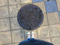 Weibliche Beine, die vor einem verzierten Einsteigeloch in Osaka stehen stockfotografie