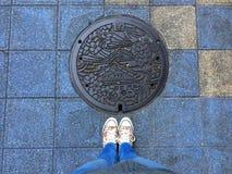 Weibliche Beine, die vor einem verzierten Einsteigeloch in Osaka stehen stockfoto
