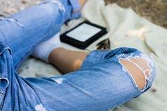 Weibliche Beine in heftigen Jeans, im elektronischen Buch und in den Gläsern auf dem Na Lizenzfreie Stockfotos