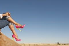 Weibliche Beine im hohen Absatz beschuht das Sitzen entspannt in der Natur Lizenzfreies Stockbild