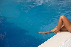 Beine im Pool Stockfotos