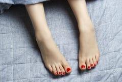 Weibliche Beine mit roter Maniküre auf dem Bett Draufsicht, Konzept des gesunden Schlafes stockfotos