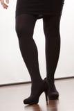 Weibliche Beine in schwarze Strumpfhose auf den Fersen gefolgten Schuhen Stockbilder