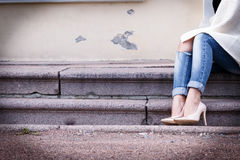 Weibliche Beine Stöckelschuhen eines in den schönen Pfirsiches mit Gold riechen Nahaufnahme Hände korrigierten Jeans Stockfoto
