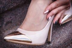 Weibliche Beine Stöckelschuhen eines in den schönen Pfirsiches mit Gold riechen Nahaufnahme Hände korrigierten Jeans Lizenzfreie Stockfotos