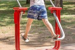 Weibliche Beine tut Übungen am Simulator im Park stockbild